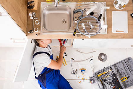 High Angle View Of Male Plumber In Overall Fixing Sink Pipe